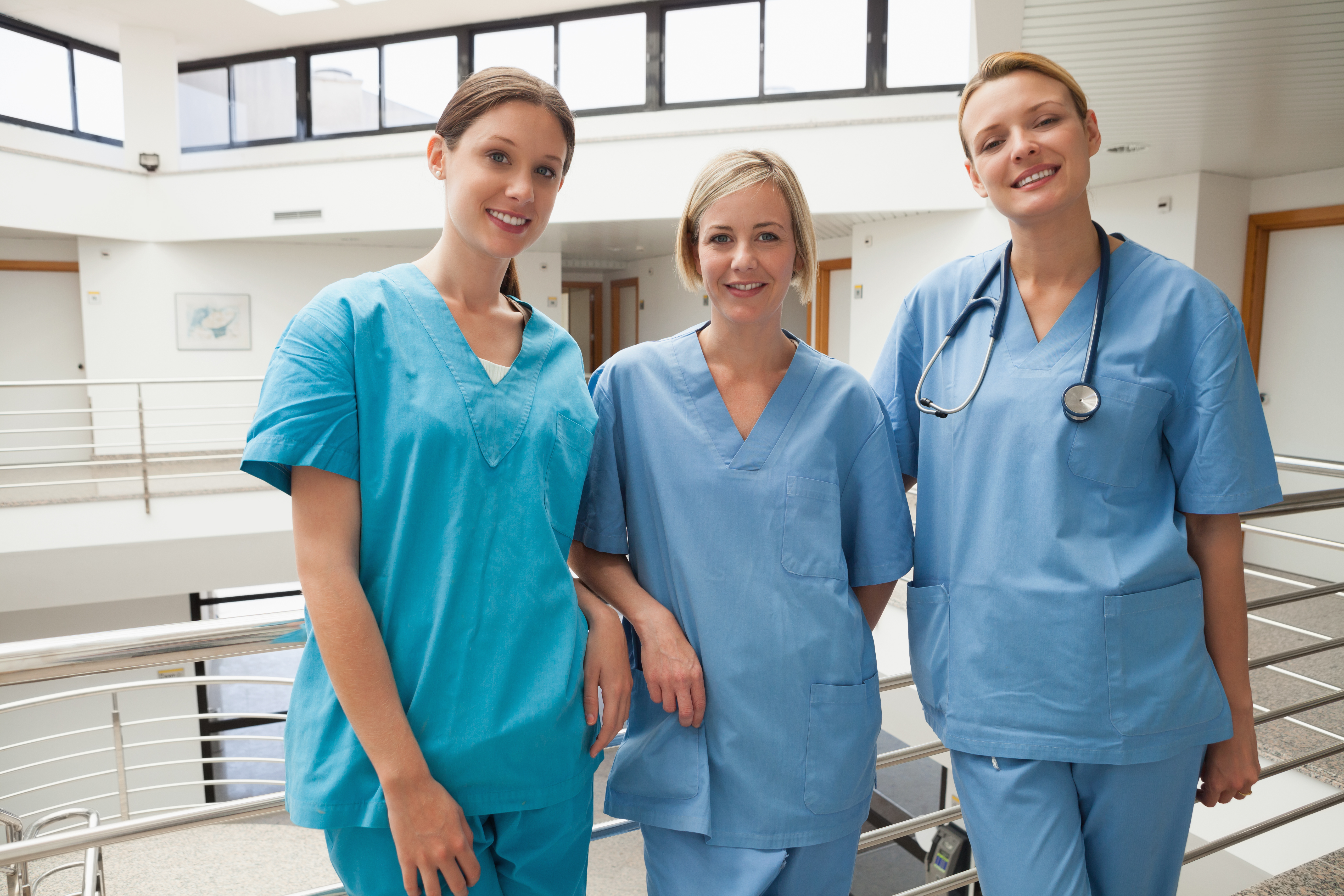 3 nurses smiling while working in the hospital