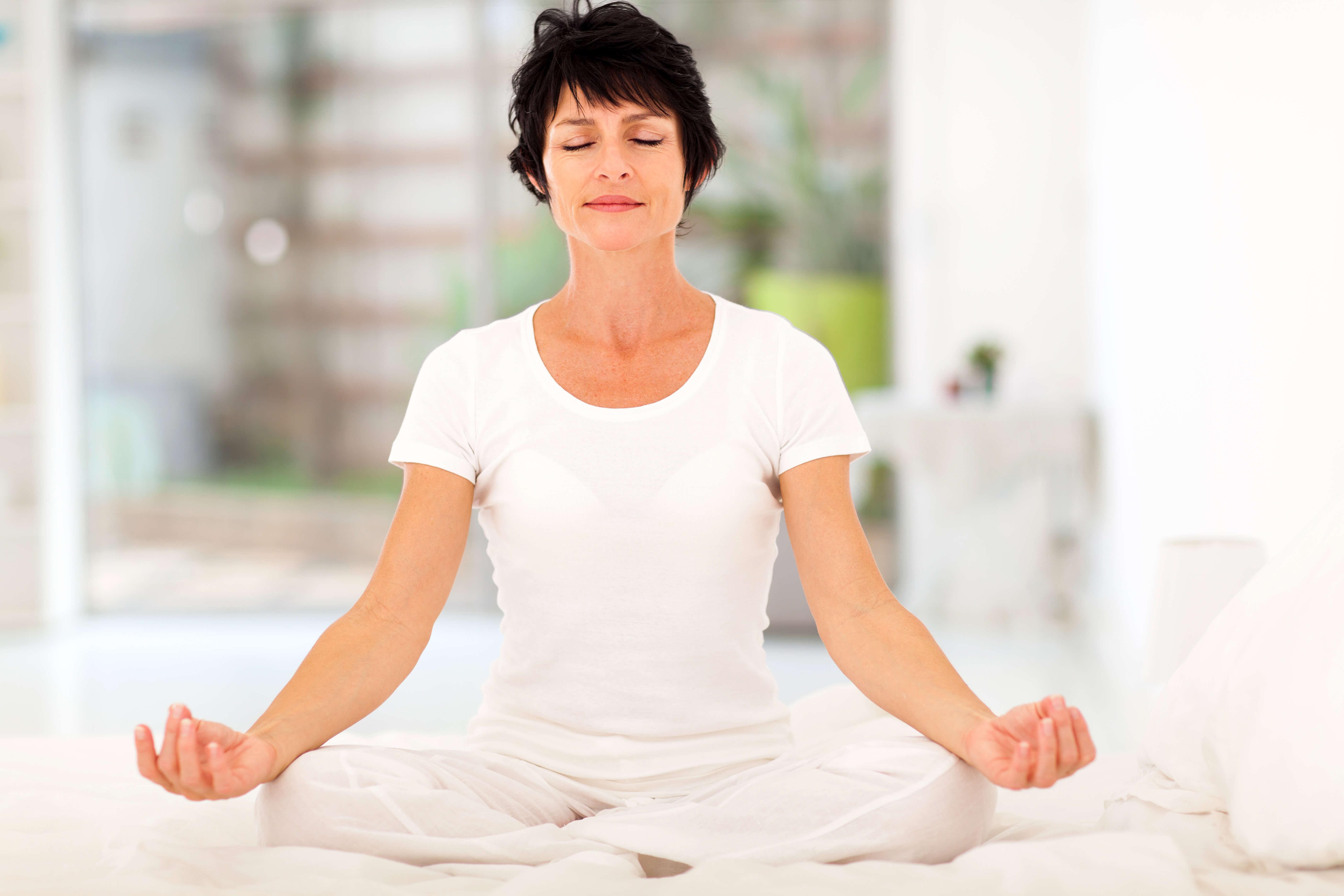 Women meditating on bed