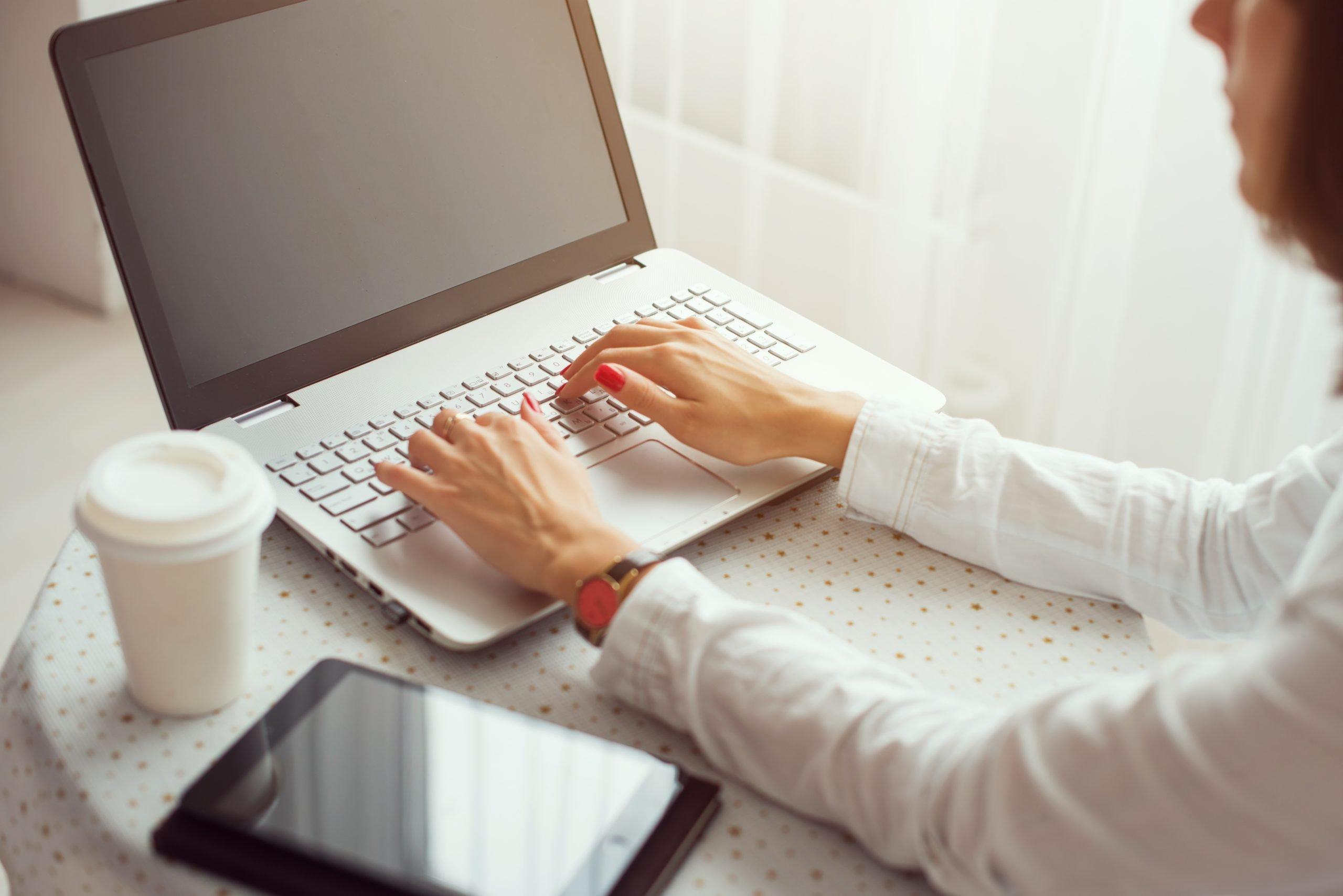 freelance writer typing on laptop at home