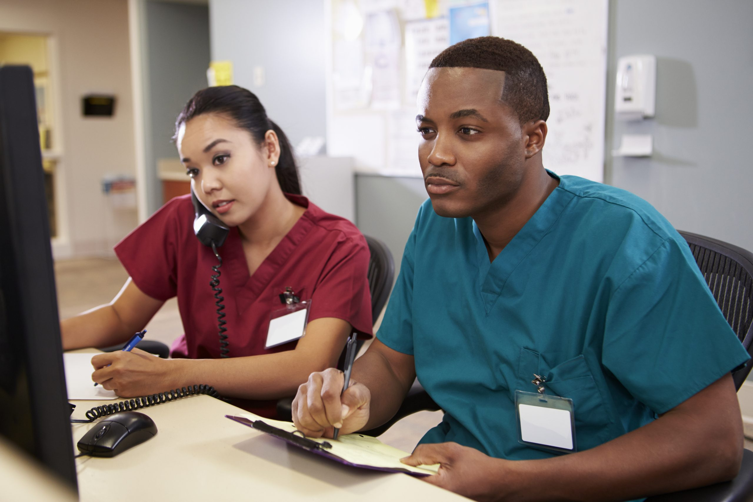 black male and asian female nurses at nursing station